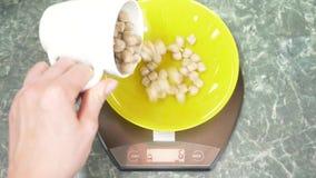 Iemand meet de zemelen in elektronisch formulier in de keuken 4k, stock video