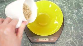 Iemand meet elektronisch ongepelde rijst in de keuken 4k, stock video