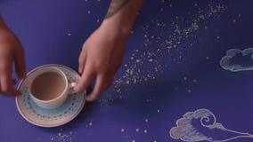 Iemand neemt uit een lijst in de vorm van een nachthemel wordt gemaakt, een mok koffie, close-up dat stock videobeelden