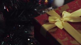 Iemand plaatste een prentbriefkaar bovenop een doos van de Kerstmisgift dichtbij Kerstmisboom stock footage