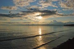 Il sole di regolazione è riflesso nell'acqua della lama del lago. Immagine Stock