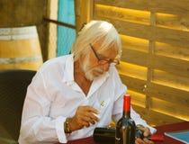 Ierre Richard que autografa garrafas em sua adega Imagens de Stock