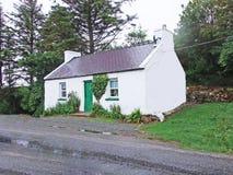 Iers plattelandshuisje door de kant van de weg Stock Afbeeldingen