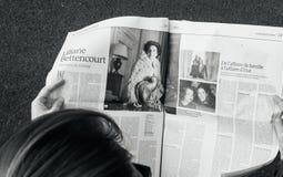 iew сверху женщины читая самую последнюю газету Le Monde с p Стоковое Фото