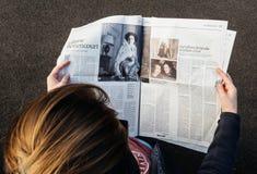 iew сверху женщины читая самую последнюю газету Le Monde с p Стоковое Изображение