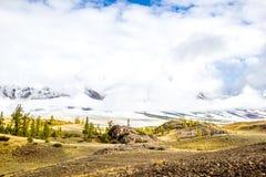 iew des Gebirgszugs unter den starken Wolken Gestalten Sie mit Hügeln, Kiefer in einem Gebirgstal landschaftlich lizenzfreies stockbild