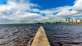 View of the river Shannon with calm waters with a small pier and buildings of Athlone village in the background. Wonderful spring day in the county of royalty free stock images