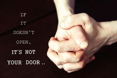 If it doesn`t open-it`s not your door. Motivation inspirational quote with man`s strong hands clasped in concentration, thinking or make decision on dark Royalty Free Stock Images