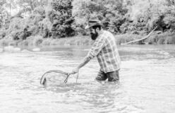 If fish regularly you know how rewarding and soothing fishing is. Bearded brutal fisher catching trout fish with net