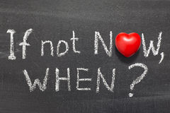 If not now, when. Question handwritten on chalkboard with heart symbol instead of O Stock Image