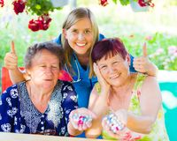 If it`s neccessary administrate it!. Thumbs up from nurse at nursing home with pensioner women holding daily medication Royalty Free Stock Image