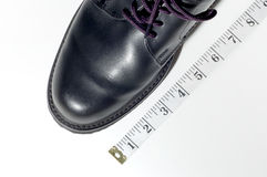 If the shoe fits. Closeup of dress shoe and tape measure stock photos