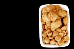 Eat apricot kernels in plates, on black ground, Sweet apricot seeds Royalty Free Stock Images
