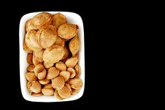 Eat apricot kernels in plates, on black ground, Sweet apricot seeds Royalty Free Stock Photography