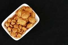Eat apricot kernels in plates, on black ground, Sweet apricot seeds Stock Images