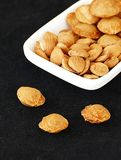 Eat apricot kernels in plates, on black ground, Sweet apricot seeds Royalty Free Stock Photo