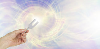 If you could see the sound waves make by an Angel Tuning Fork. Female hand holding a short aluminum tuning fork on a graphic depiction of angelic sound waves Stock Photo