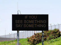 If You See Something Say Something. A sign near a major airport urges citizens to report suspicious activity Royalty Free Stock Photos
