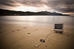 If you were on a stranded island... An old computer abandoned on a beach during winter. It also reminds me the popular If you were stranded on an island what is Royalty Free Stock Photography