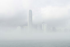 IFC in misty. Morning view from Star Ferry pier in Tsim Sha Tsui, Kowloon Royalty Free Stock Photography