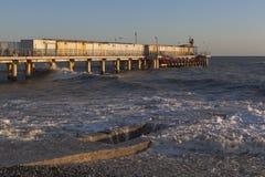 Ig-Welle bedeckte Wellenbrecher am Pier in der Erholungsortregelung von Adler in der untergehenden Sonne Lizenzfreies Stockfoto