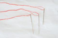 Igły z czerwonymi niciami fotografia stock