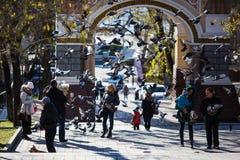 Igeons altísimo contra el contexto de la gente en el arco de Tsesarevich en Vladivsotok imágenes de archivo libres de regalías