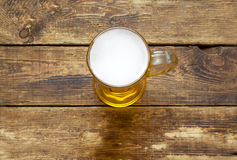 Ight beer mug with foam. On the wooden surface.view from above Stock Photo