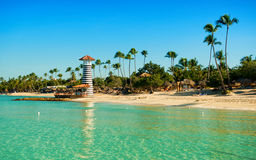 Ighthouse on a sandy tropical island with palm trees. Stock Photo