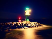 The ighthouse shinning at port gate. Modern light house at the end of stony pier Stock Image