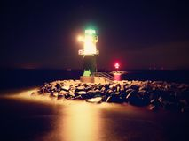 The ighthouse shinning at port gate. Modern light house at the end of stony pier Royalty Free Stock Photo