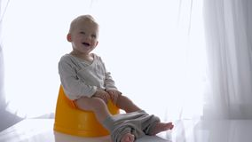 Igiene dei bambini, infante felice che si siedono su banale e sorrisi nella stanza luminosa archivi video