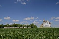 Iglesia abandonada rodeada por el campo de la haba foto de archivo libre de regalías
