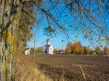 Iglesia al borde del campo arado Imagenes de archivo