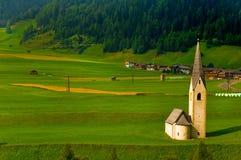 Iglesia alpestre minúscula en campo verde foto de archivo