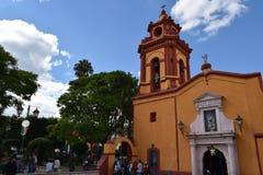 Iglesia amarilla y anaranjada en un pueblo mágico fotografía de archivo
