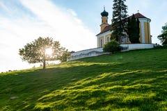 Iglesia bávara en una colina con un árbol outshined imagen de archivo