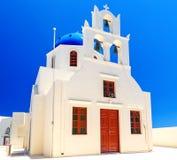 Iglesia blanca hermosa ortodoxa griega con un campanario contra el cielo azul claro en el pueblo de Oia en Santorini Fotos de archivo libres de regalías