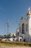 Iglesia blanca ortodoxa cristiana del edificio con las bóvedas y las cruces del oro por la grúa de construcción Imágenes de archivo libres de regalías