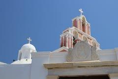 Iglesia blanca y color de rosa agradable con el cielo azul en Fira Thira Santori foto de archivo libre de regalías