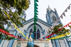 Iglesia católica azul adornada con las banderas y la estatua de St Mary Fotografía de archivo