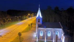 Iglesia con vista nocturna del top así como la avenida encendida imagenes de archivo