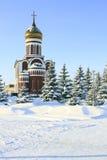 Iglesia contra el cielo azul y el abeto nevado Fotografía de archivo