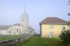 Iglesia de la abadía en el Jura, Francia y la curación (casa del sacerdote). Foto de archivo libre de regalías