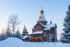 Iglesia de madera en bosque nevoso del invierno en la puesta del sol Imagenes de archivo
