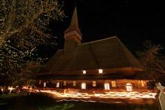 Iglesia de madera rodeada por la gente con la vela encendida Fotos de archivo