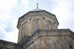 Iglesia de piedra amarilla encima de la montaña en Stepantsminda, en Georgia fotografía de archivo