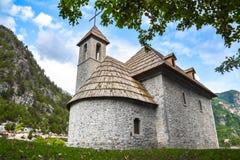 Iglesia de piedra con el tejado de madera en el pueblo de montaña foto de archivo libre de regalías