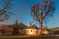 Iglesia del pueblo con un árbol viejo por otra parte Fotografía de archivo libre de regalías