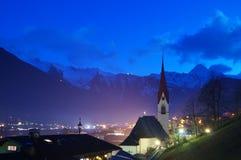 Iglesia delante de las montañas en la noche Foto de archivo